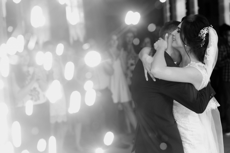 happy gorgeous wedding couple having first dance at wedding party in restaurant reception with fireworks. romantic moment of emotional bride and stylish groom dancing. space for text
