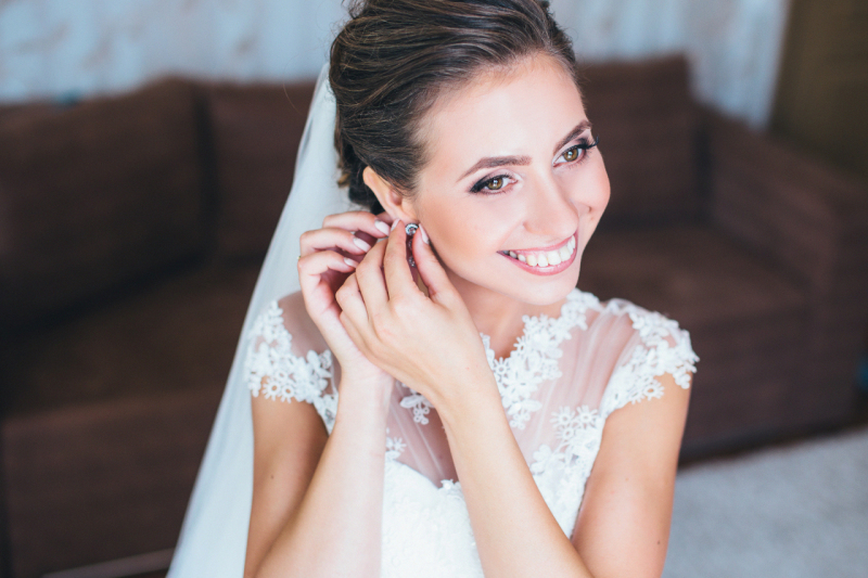 Bride-putting-earring-on