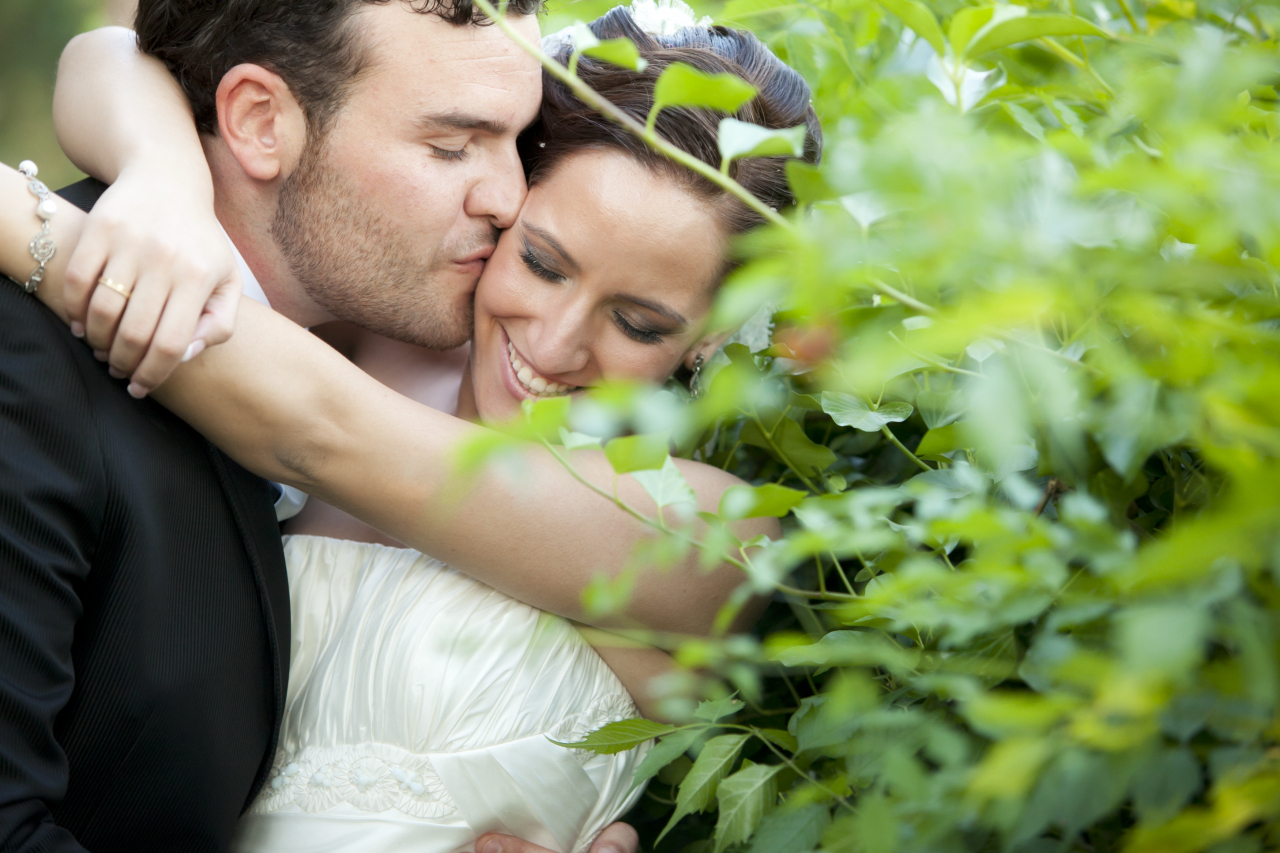 Bride and Groom sneaky kiss on the cheek